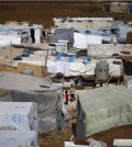 syrian-refugees-stand-outside-their-tents-at-a-syrian-refuge